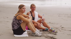 Two women resting and drinking water after run Stock Footage