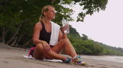 Woman resting and drinking water after run Stock Footage