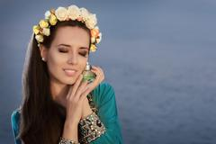 Young Woman With Floral Wreath Holding Perfume Bottle in Seaside Landscape Stock Photos