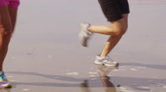 Two women running together on beach - stock footage
