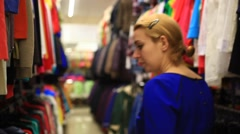 Woman shopping clothes. Shopper looking at clothing indoors in store. Beautiful Arkistovideo