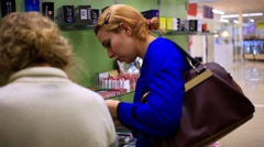 Young blonde woman consults and shopping in the women's cosmetics store, selects Stock Footage