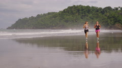 Slow motion shot of two women running on beach - stock footage