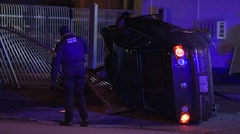 Vehicle On Its Side After A Crash And Police Officer Walking Through The Scene - stock footage