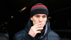 Young man smoking cigarette begins to cough after Smoking Cigarette while - stock footage