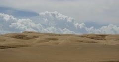 4k great white puffy cloud mass rolling over desert sand dunes. Stock Footage