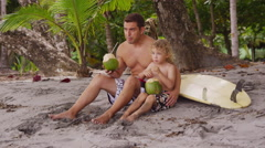 Father and son at beach drinking coconut milk Stock Footage
