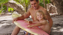 Portrait of father and son with surfboard - stock footage