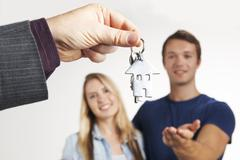 Estate Agent Handing Over House Keys To Young Couple Stock Photos