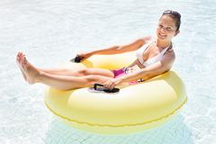 Happy Woman Relaxing On Inner Tube In Swimming Pool Stock Photos