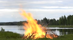 Big midsummer fire at the bank off forest lake on Saint John day - stock footage
