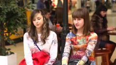 Two teen age girls on a bench in a big shopping center Stock Footage