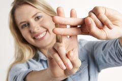 Pretty Girl Making Hashtag Sign With Fingers - stock photo