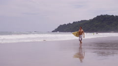 Man with surfboard walking at beach - stock footage