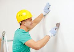 Smiling man in helmet doing renovations at home Stock Photos
