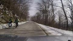 Passing bicyclist snowy mountain road Stock Footage