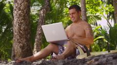 Surfer using laptop on beach, Costa Rica Stock Footage