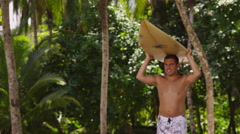 Surfer carrying surfboard at beach, Cost Rica - stock footage