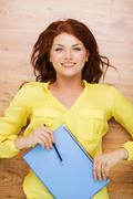 Smiling female student with textbook and pencil Stock Photos