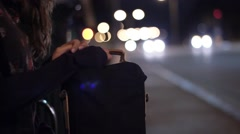 Girl with bag waiting for bus at bus stop Stock Footage