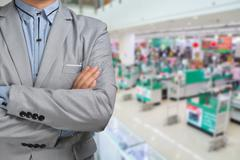 Business Man stand in Hypermarket or Supermarket store present retail marketi Stock Photos