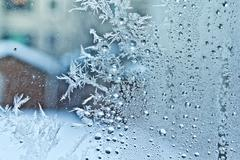 Ice crystals on a glass window - stock photo