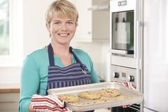 Woman In Kitchen Holding Tray With Home Baked Cookies Stock Photos