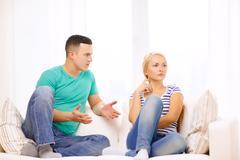 Unhappy couple having argument at home Stock Photos