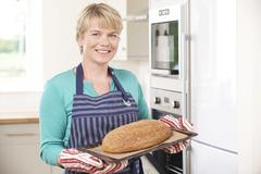 Woman Taking Home Baked Loaf Out Of Oven Stock Photos