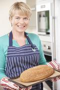 Woman In Kitchen Holding Tray With Home Made Loaf Of Bread Stock Photos
