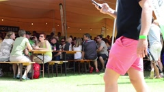 People Sit on Benches Under a Tent and Drink Alcohol at a Beer Festival Stock Footage