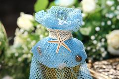 Bottle with oil decorated    with blue veil and sea star - stock photo