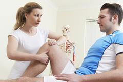 Osteopath Treating Male Patient With Sports Injury - stock photo