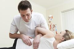 Male Osteopath Treating Female Patient With Back Problem - stock photo
