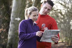 Couple Orienteering In Woodlands With Map And Compass Stock Photos