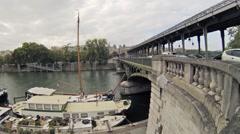 Traffic and people on Bir Hakeim bridge, yacht moored Stock Footage