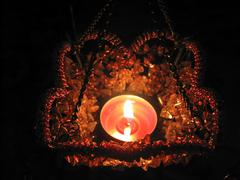 Flaming candle in basket and dark background - stock photo