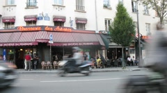 People sit near Brasserie des Artistes near road with traffic. Stock Footage