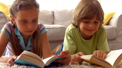 Siblings reading books on the floor Stock Footage
