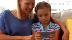 Daughter playing game on phone with mother Arkistovideo