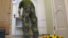 Two workers assemble the cabinet shelves near the door. Stock Footage