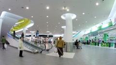 People in hall with escalator of modern shopping center Auchan Stock Footage