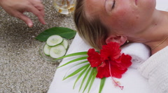 Woman at spa gets cucumbers put over eyes Stock Footage