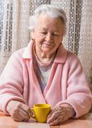 Portrait of old woman with cup of tea - stock photo