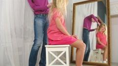 Hairdresser braids hair girl sitting on a chair near mirror - stock footage
