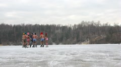Shoot video of cheerful boys and girls, skating on frozen pond Stock Footage