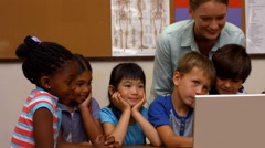 Cute pupils looking at laptop with teacher Stock Footage