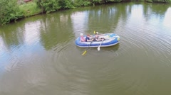 Three kids boys and little girl sail on inflated boat by pond Stock Footage