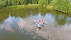 Four kids boys and little girls play on inflated boat on pond Stock Footage