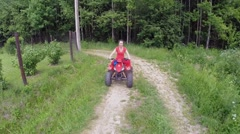 Woman drives on quad bike by country road near forest at summer Stock Footage